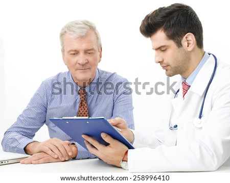 Portrait of young mail doctor consulting with eldery patient while sitting against white background.  - stock photo