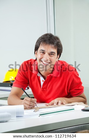 Portrait of young male architect drafting blueprint while sitting at desk