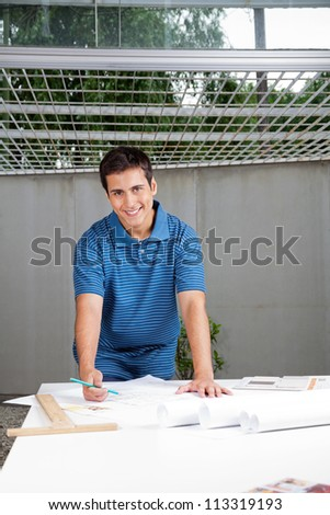 Portrait of young male architect in casual wear working on blueprints