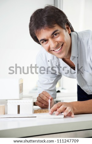 Portrait of young male architect smiling while creating a model house