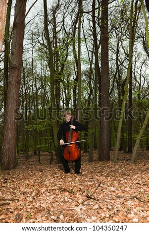Portrait of young male cello player in green spring forest. Blond hair. Playing classic instrument. Dressed in black. Artistic looking.