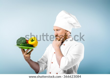 Portrait of young male chef in white uniform. Head-cook carefully looking at plate with fresh vegetables and standing against grey background - stock photo