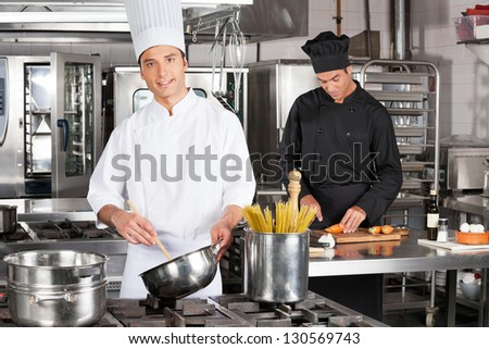 Portrait of young male chef preparing spaghetti with colleague chopping carrots in kitchen