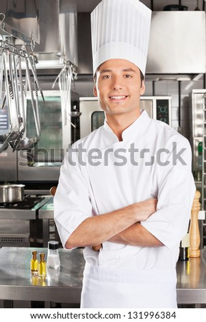 Portrait of young male chef with arms crossed in restaurant kitchen - stock photo
