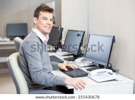 Portrait of young male customer service representative working in office - stock photo