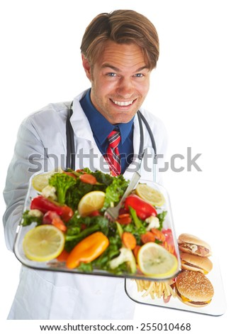 Portrait of young male doctor holding dishes of healthy and unhealthy food over white background - stock photo