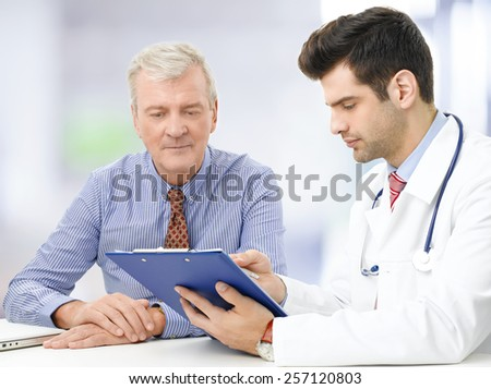 Portrait of young male doctor sitting at desk with elderly patient and consulting at hospital.