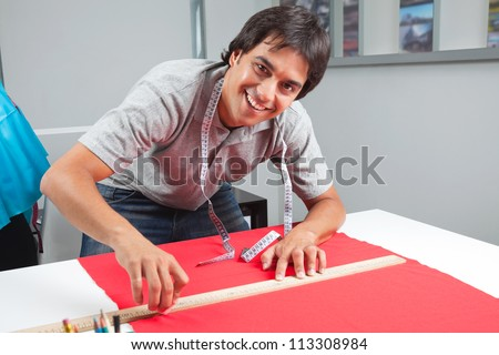 Portrait of young male dressmaker measuring a red fabric with ruler on table - stock photo