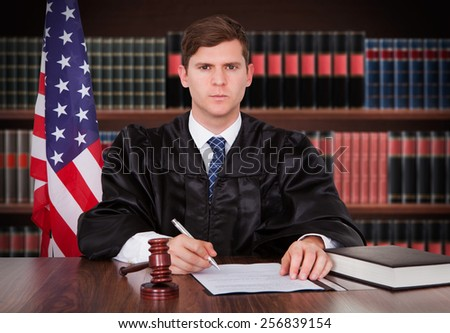 Portrait Of Young Male Judge Sitting In Courtroom - stock photo