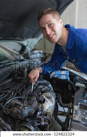 Portrait of young male mechanic working under bonnet of car