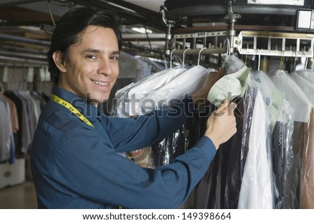 Portrait of young male owner checking clothes tag in laundry - stock photo