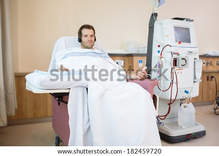 Portrait of young male patient listening to music while receiving renal dialysis treatment in hospital room - stock photo
