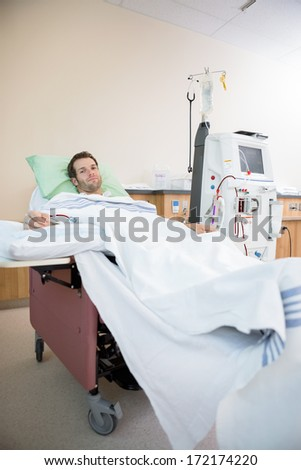 Portrait of young male patient receiving renal dialysis in hospital room - stock photo