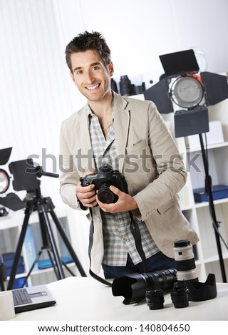 Portrait of young male photographer with professional digital camera - stock photo