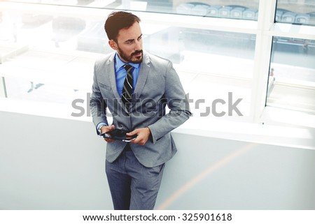 Portrait of young male professional worker dressed in corporate clothing holding touch pad while standing in office building, successful man entrepreneur dressed in elegant suit using digital tablet  - stock photo