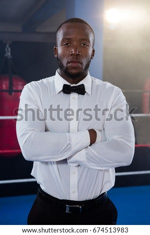 Portrait of young male referee standing with arms crossed in boxing ring