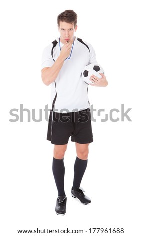 Portrait Of Young Male Soccer Referee Holding Football And Blowing Whistle - stock photo