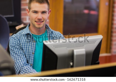 Portrait of young male student using computer in the computer room - stock photo