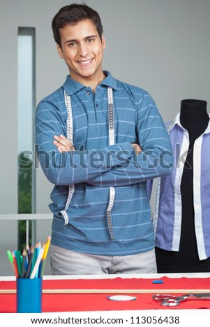Portrait of young male tailor standing arms crossed by table with mannequin in background - stock photo