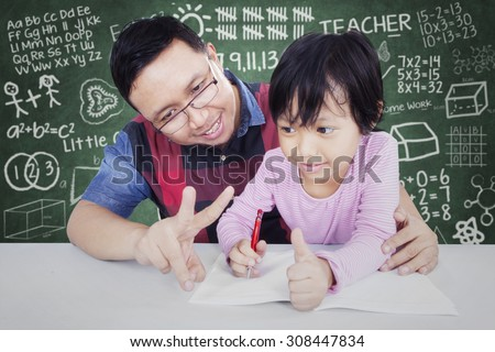 Portrait of young male teacher teach his female elementary school student to calculate with her finger in the classroom - stock photo