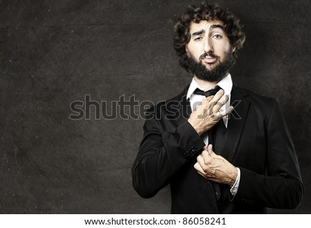 portrait of young man adjusting his suit against a grunge background