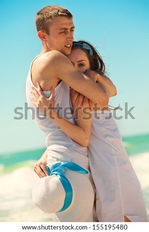 Portrait of young man and woman embracing as a happy romantic couple on a beach. Couple enjoying a summer vacation. - stock photo