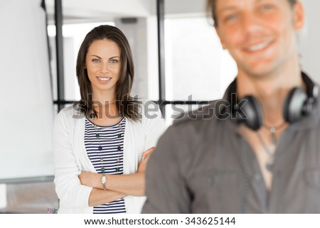 Portrait of young man and woman in bright office