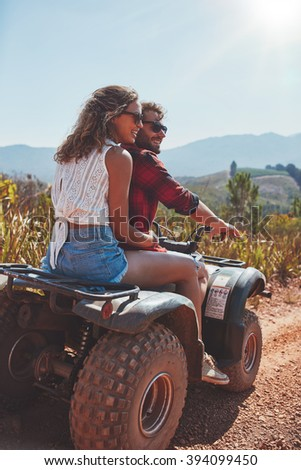 Portrait of young man and woman in nature on a off road vehicle. Young couple enjoying a quad bike ride in countryside. - stock photo