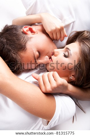 Portrait of young man and woman lying on floor and kissing - stock photo