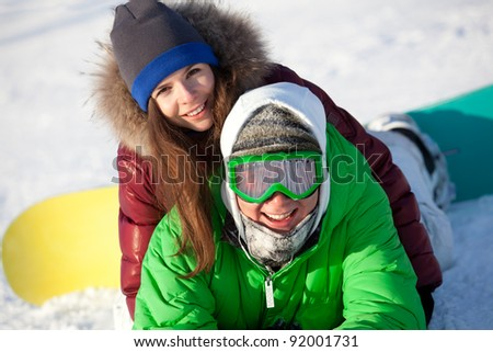 portrait of young man and woman relaxing on the snow with snowboard - stock photo