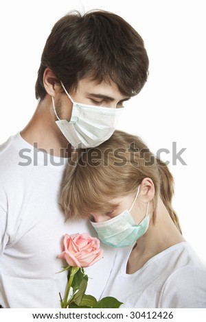 Portrait of young man and woman wearing masks  in tight embrace - stock photo