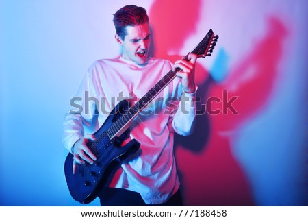 Portrait of young man artist singing, screaming, playing electric guitar Hobby, music concept. Rock Star