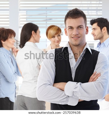 Portrait of young man at office in front of talking business team. - stock photo