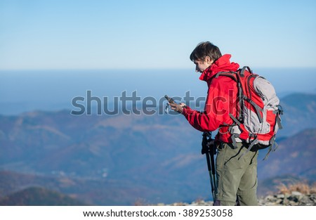 Portrait of young man backpacker standing on the peak of the mountain and looking at gps coordinates. Beautiful mountains on the background. Tourist wearing red jacket and red backpack. - stock photo