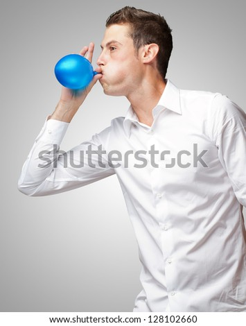 Portrait Of Young Man Blowing A Balloon Over Grey Background