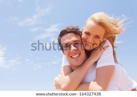 portrait of young man carrying girlfriend on his back - stock photo