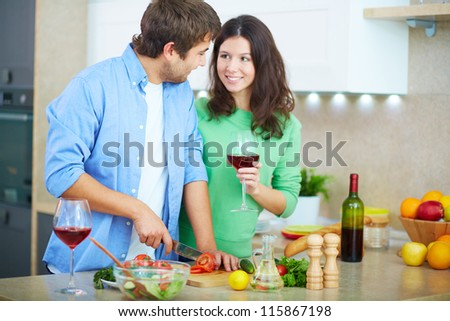 Portrait of young man cooking salad and looking at his wife with glass of red wine in the kitchen - stock photo
