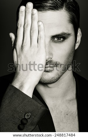 Portrait of young man covering his right eye with her hand on a black background. Studio shot - stock photo