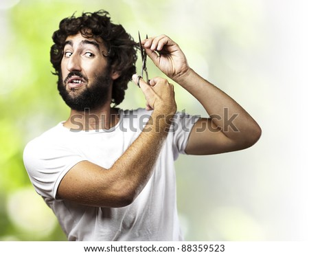 portrait of young man cutting the hair against a plants background - stock photo
