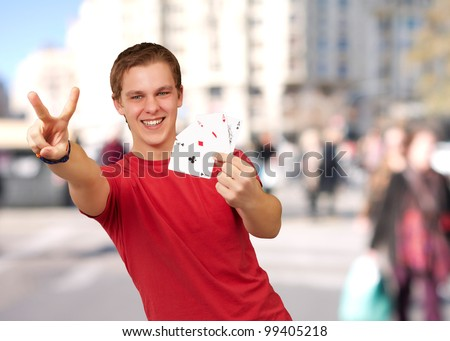 portrait of young man doing a victory gesture playing poker at crowded city