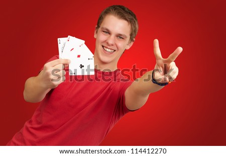 portrait of young man doing a victory gesture playing poker over red background