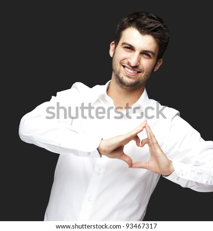 portrait of young man doing heart gesture against a black background