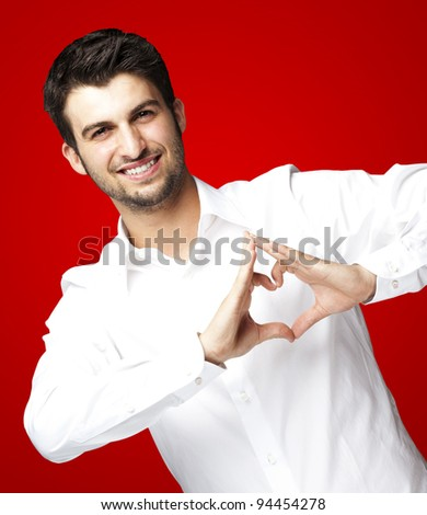 portrait of young man doing heart gesture against a red background - stock photo