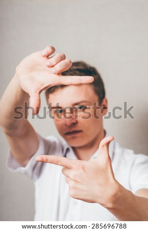 portrait of young man doing photo gesture over grey background - stock photo