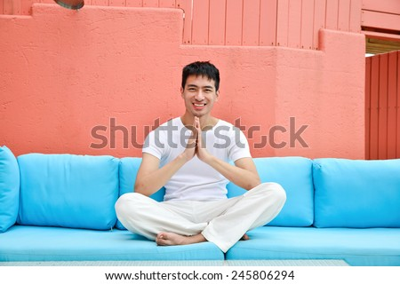 portrait of young man doing yoga in lotus, sitting in living room. - stock photo