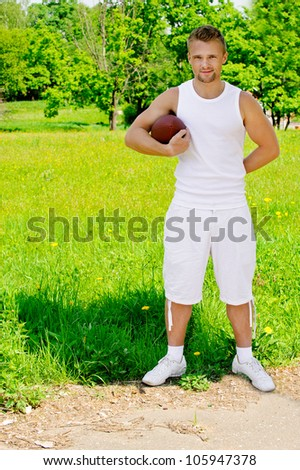 Portrait of young man dressed in white sportsman with rugby ball, against green of summer park.