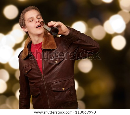portrait of young man drinking beer against an abstract lights background