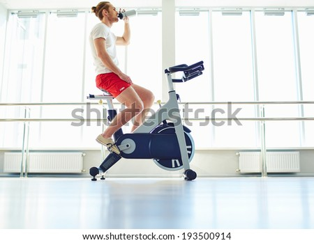 Portrait of young man drinking water while sitting on special sport equipment in gym - stock photo