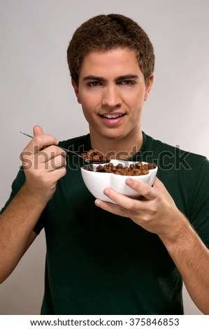 Portrait of young man eating cereal