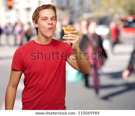 portrait of young man eating pizza portion at crowded street